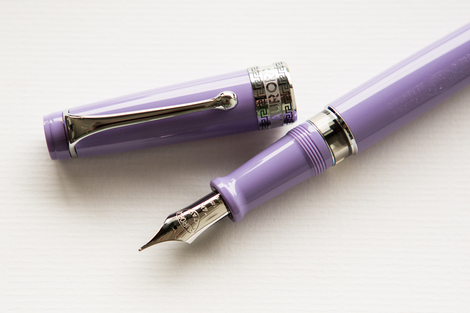 Aurora Optima flex in a summery spread of pink, purple, and orange fountain pens and accessories.