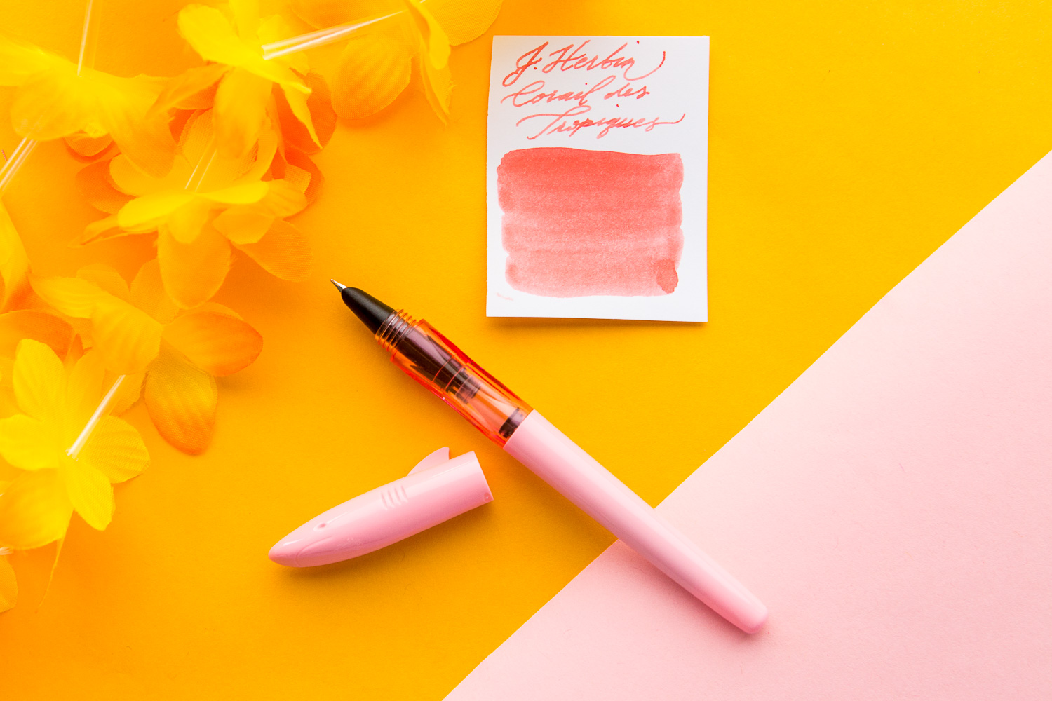 Jinhao shark fountain pen in a summery spread of pink, purple, and orange fountain pens and accessories.