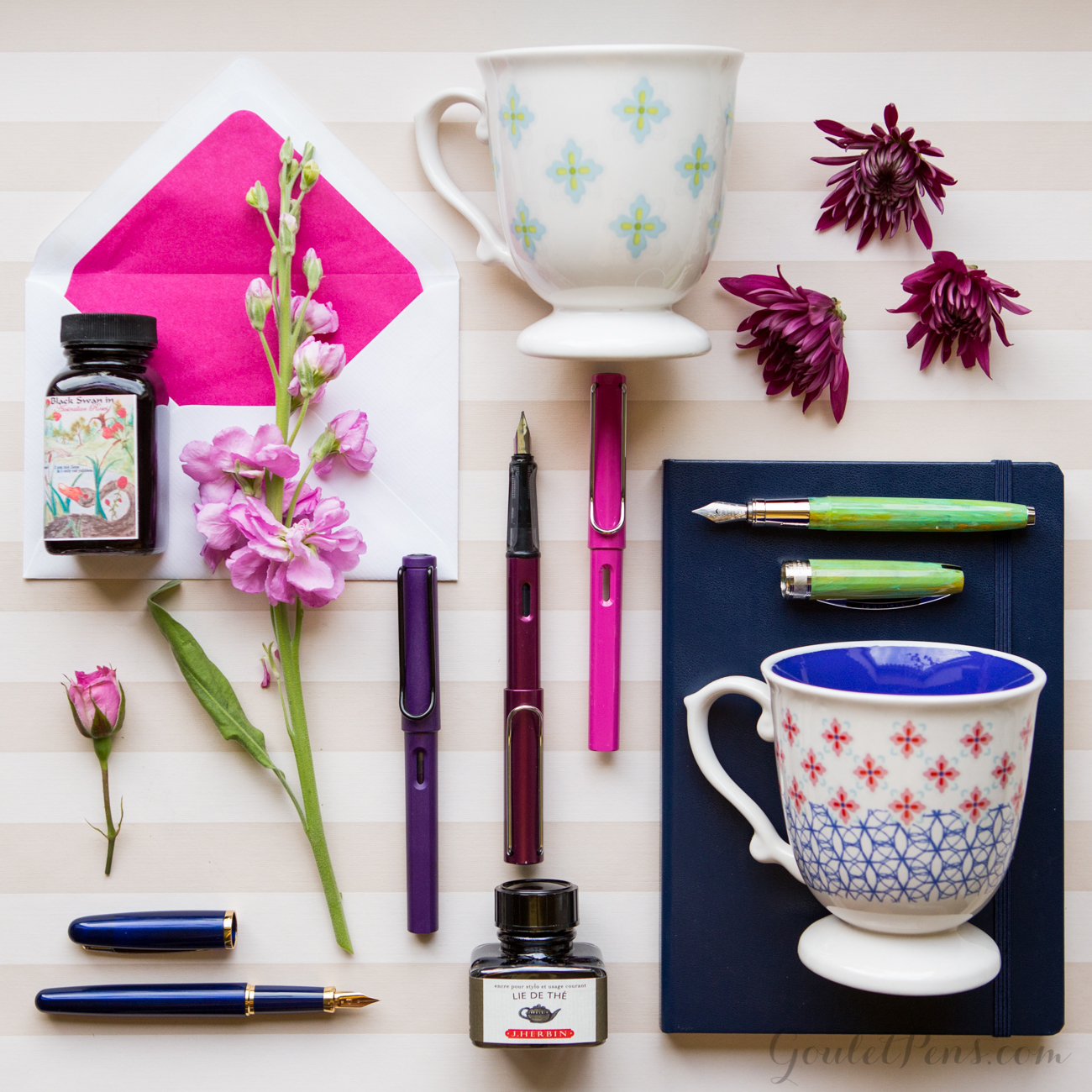 A tea party themed flat lay arrangement of fountain pens, notebooks, and ink in an array of pink, purple, and floral hues.