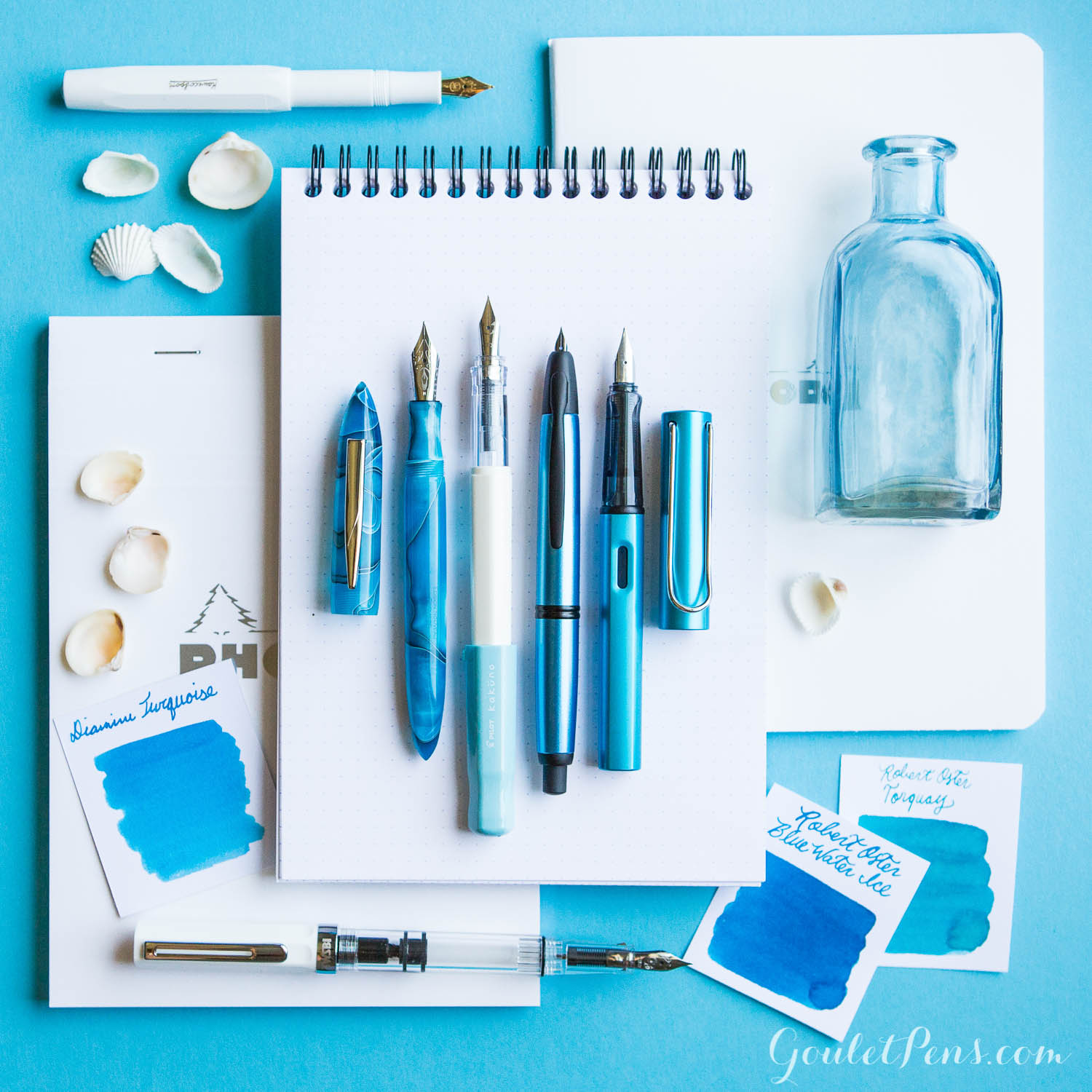A turquoise and sea inspired flat lay of fountain pens, notebooks, and ink