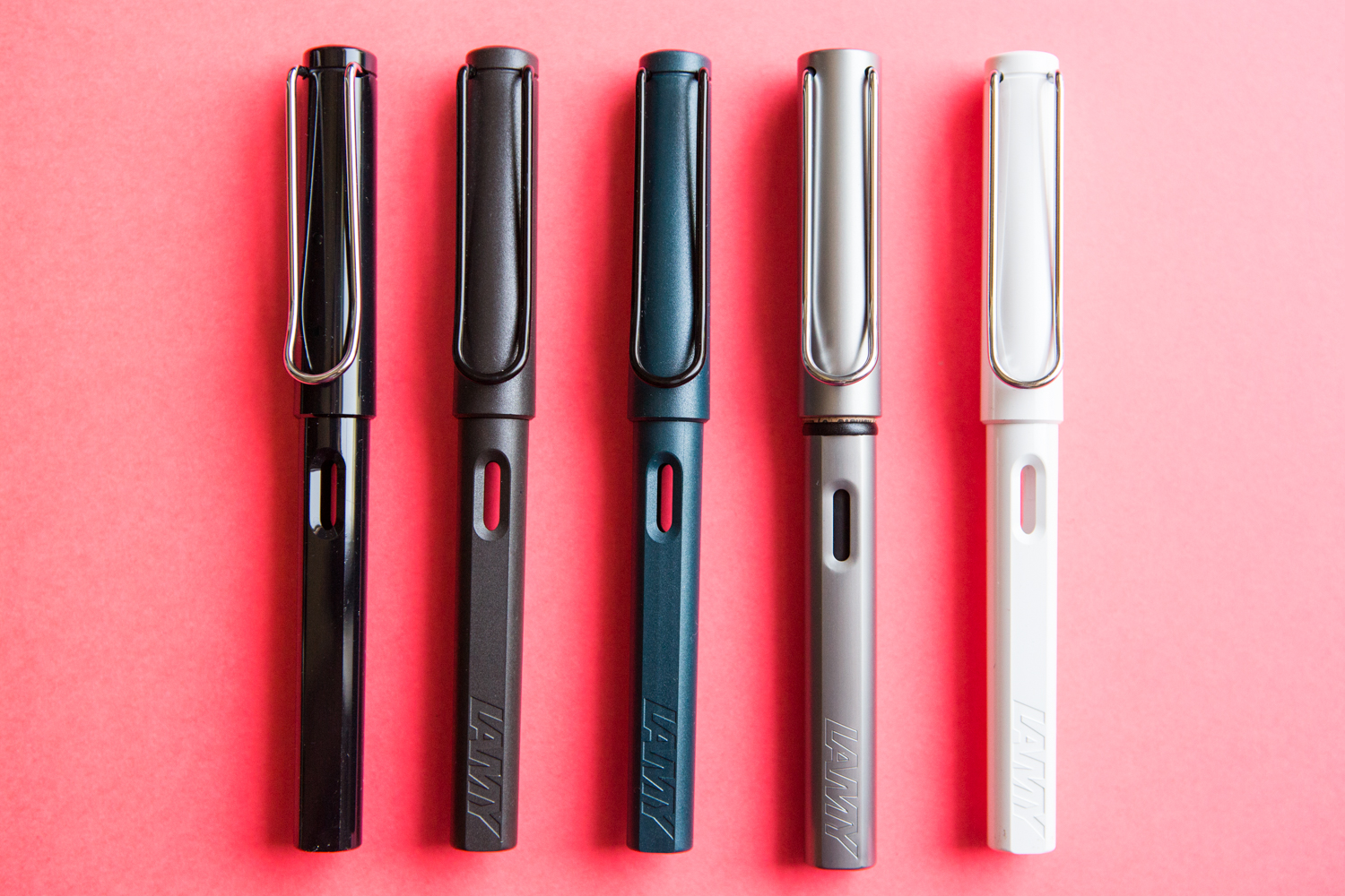 A colorful Lamy inspired flat lay of fountain pens, notebooks, and ink.