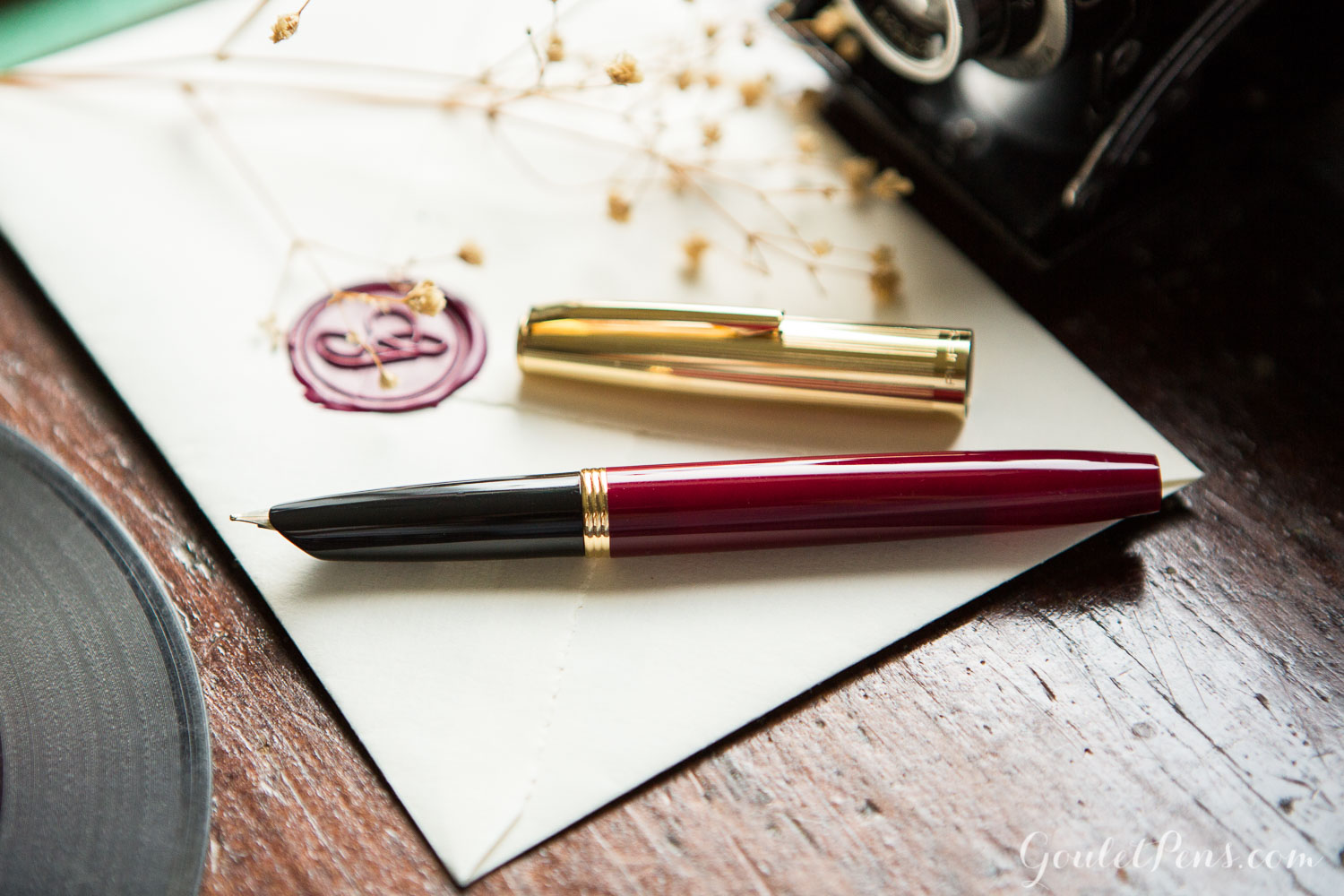 Aurora Duo Cart Bordeaux in a vintage, vinyl record inspired flat lay of fountain pens, notebooks, and ink.