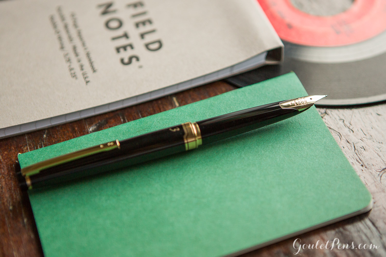 Pilot E95S Black in a vintage, vinyl record inspired flat lay of fountain pens, notebooks, and ink.