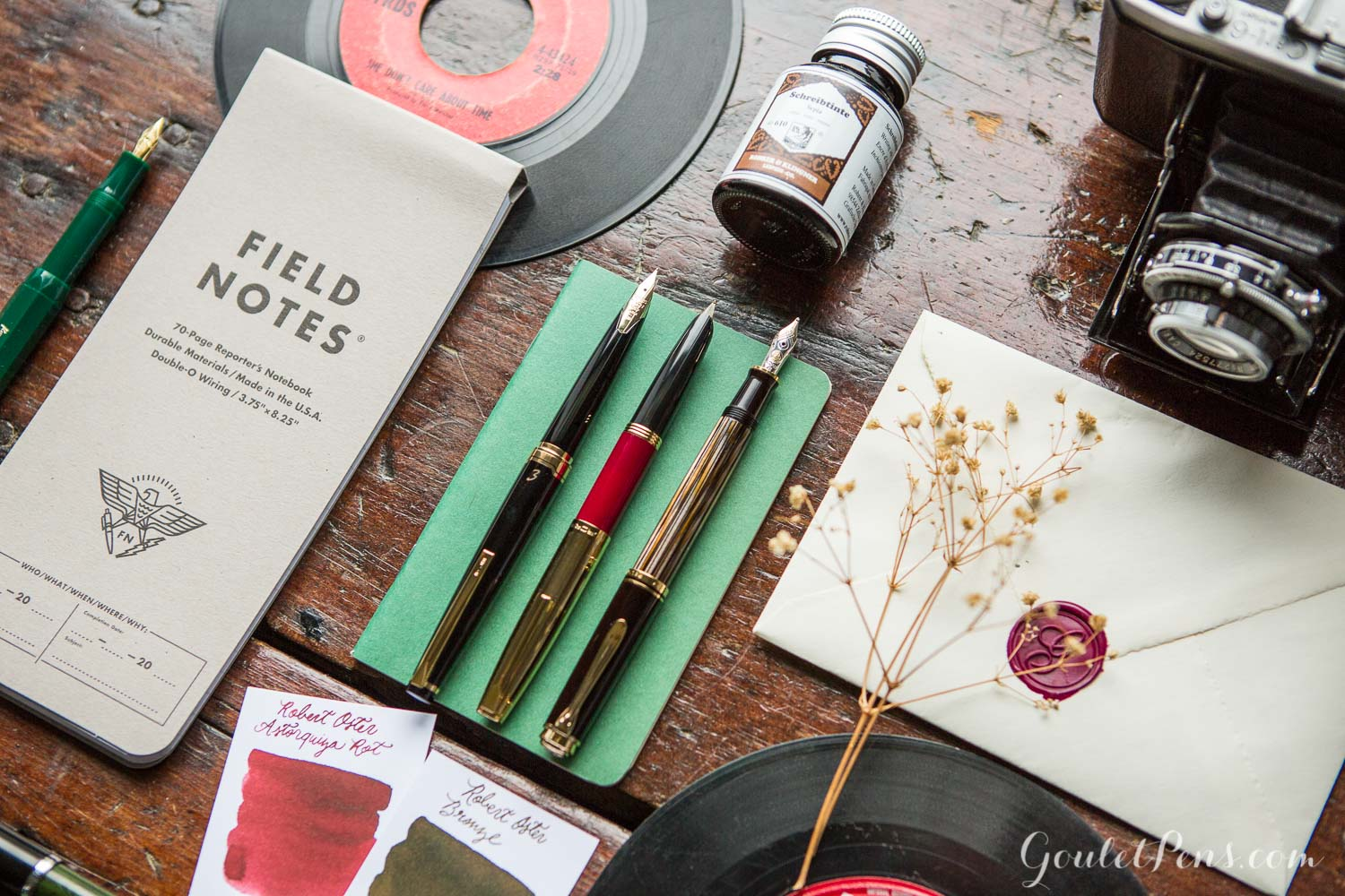 A vintage, vinyl record inspired flat lay of fountain pens, notebooks, and ink.
