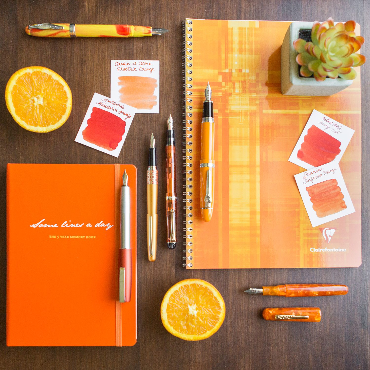An orange citrus inspired flat lay of fountain pens, notebooks, and ink.