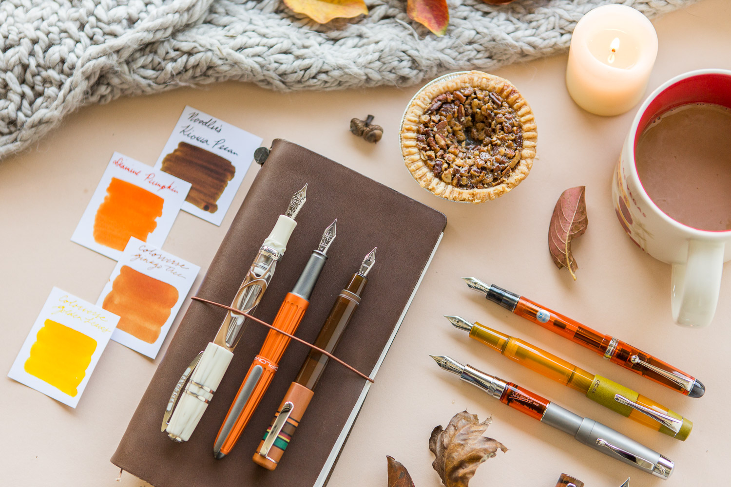 Fall themed flat lay of fountain pens, leather notebook, and ink.