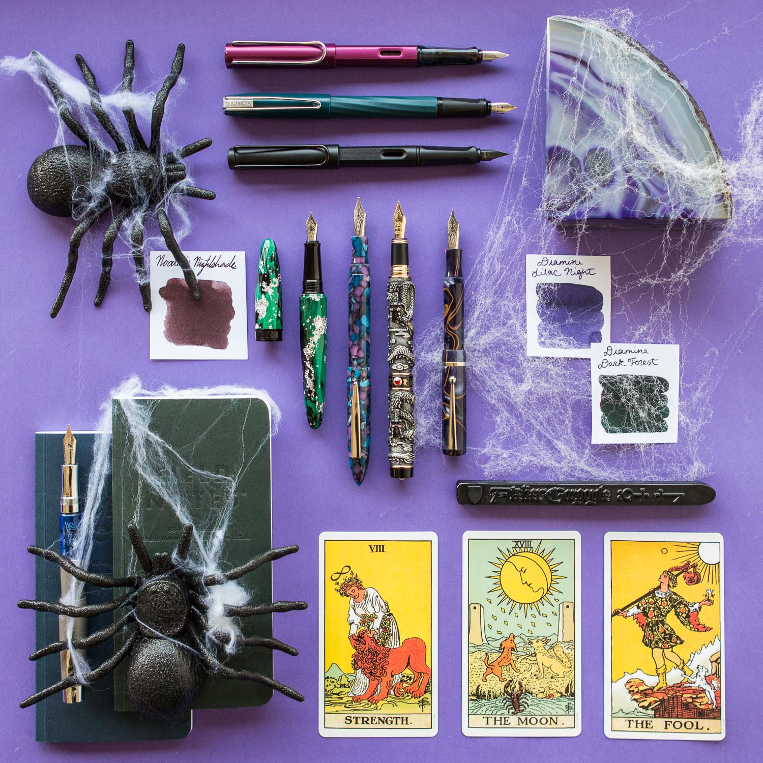 Purple halloween themed fountain pens, notebooks, and ink.