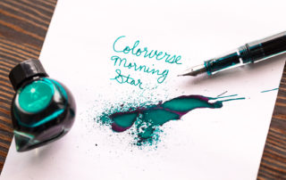A splatter of Colorverse Morning Star fountain pen ink. Ink is a greenish turquoise with a reddish sheen.